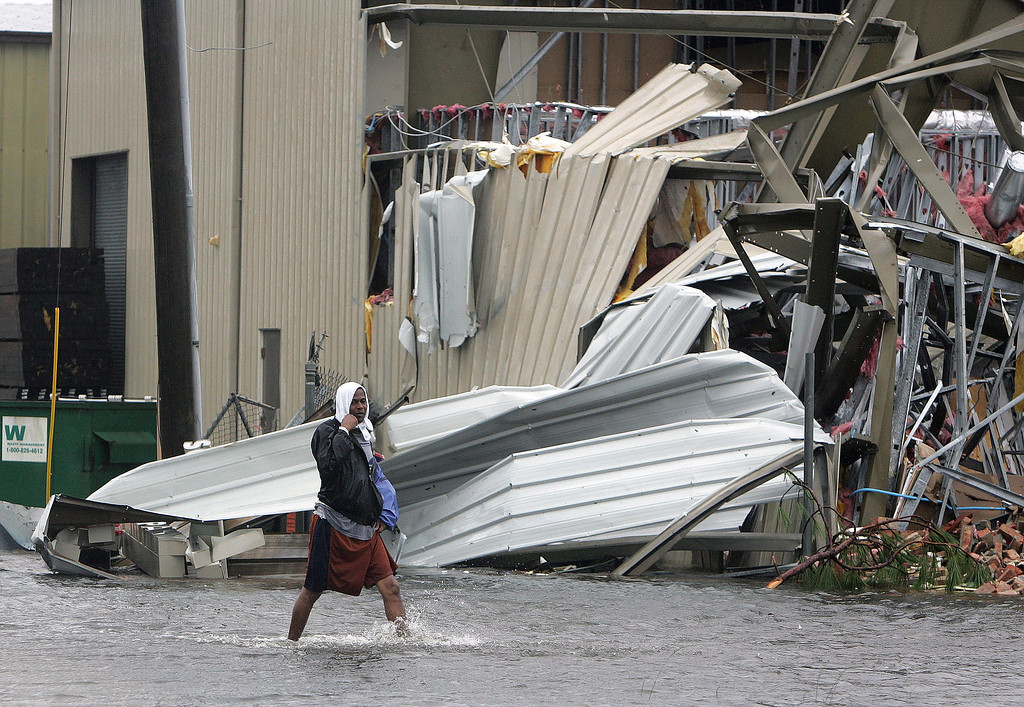 . James Smith wades past a storm damaged building after Hurricane Katrina struck the Gulf Coast Monday,  Aug. 29, 2005 in Gulfport, Miss..  (AP Photo/John Bazemore)