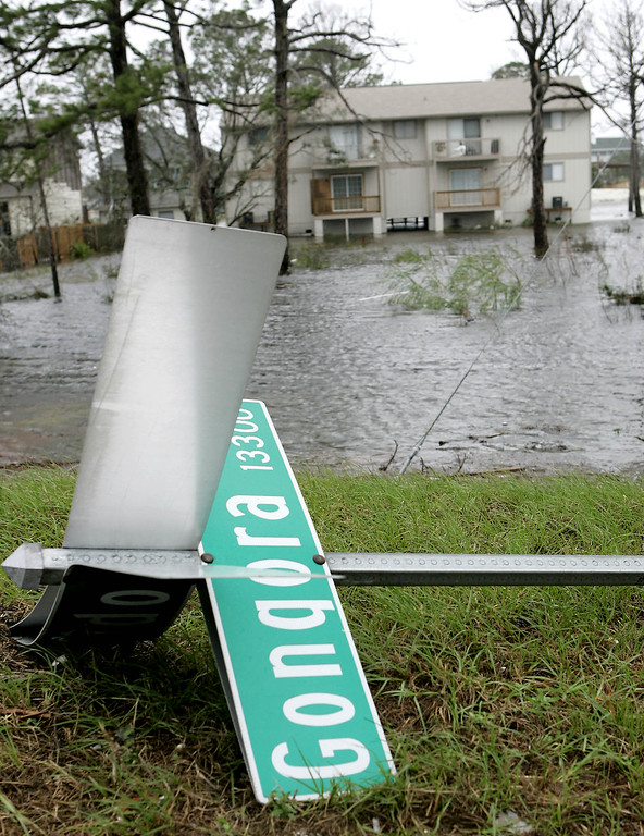 . A fallen street sign rests along the overflowing Intracoastal Waterway in Perdido Key, Fla., as the outer bands of Hurricane Katrina pass through the area, Monday, Aug. 29, 2005. (AP Photo/Peter Cosgrove)