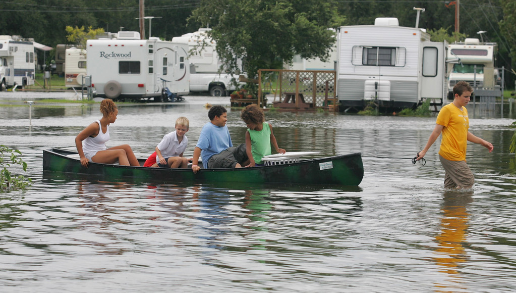 . Jordan Hale, front, pulls kids in a canoe through a flooded mobile home park in Florida City, Fla., Friday, Aug. 26, 2005. Hurricane Katrina flooded streets, darkened homes and felled trees as it plowed across South Florida before emerging over the Gulf of Mexico. (AP Photo/Luis M. Alvarez)