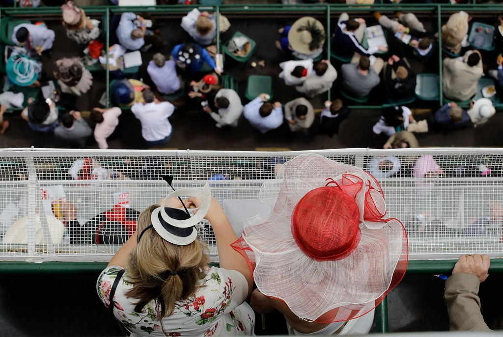 . Women in hats watch a race before the 143rd running of the Kentucky Derby horse race at Churchill Downs Saturday, May 6, 2017, in Louisville, Ky. (AP Photo/Charlie Riedel)