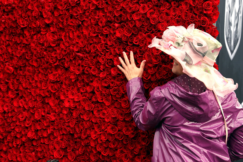 . LOUISVILLE, KY - MAY 06:  A woman wearing a festive hat poses in front of roses prior to the 143rd running of the Kentucky Derby at Churchill Downs on May 6, 2017 in Louisville, Kentucky.  (Photo by Patrick Smith/Getty Images)