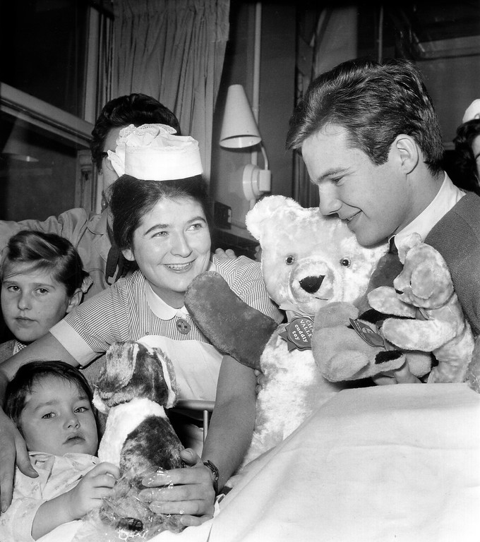 """. Bobby Vee, 19-year-old American \'Pop\"""" singer, on a three-week British tour, visits Claire Moindrot, 3 1/2 of Paris and presents her with a teddy bear during his visit, Nov. 15, 1962 at the Victoria Hospital For Children at Chelsea, London. Vee handed out some 150 dolls to young patients. He acquired the dolls from his many British fans have made a habit of tossing the dolls onto the stage after each performance."""