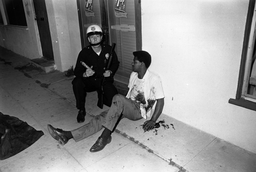 . A blood-splattered man sitting beside an armed policeman, during the Watts Riots, Los Angeles, California, 11th-15th August 1965.  (Photo by Harry Benson/Express/Getty Images)