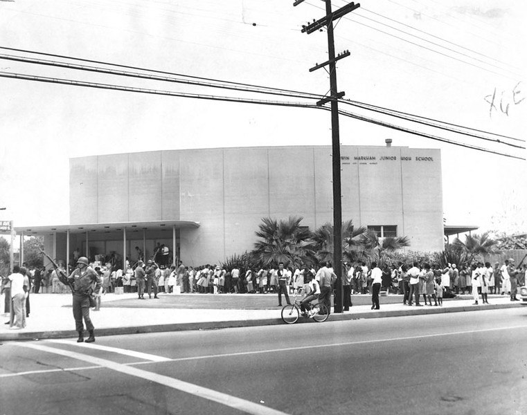 . Families from the riot areas wait in line at Edwin Markham Junior High to receive food baskets from the Salvation Army. National Guardsmen with rifles, keep watch. Photo dated August 17, 1965. (Los Angeles Public Library)