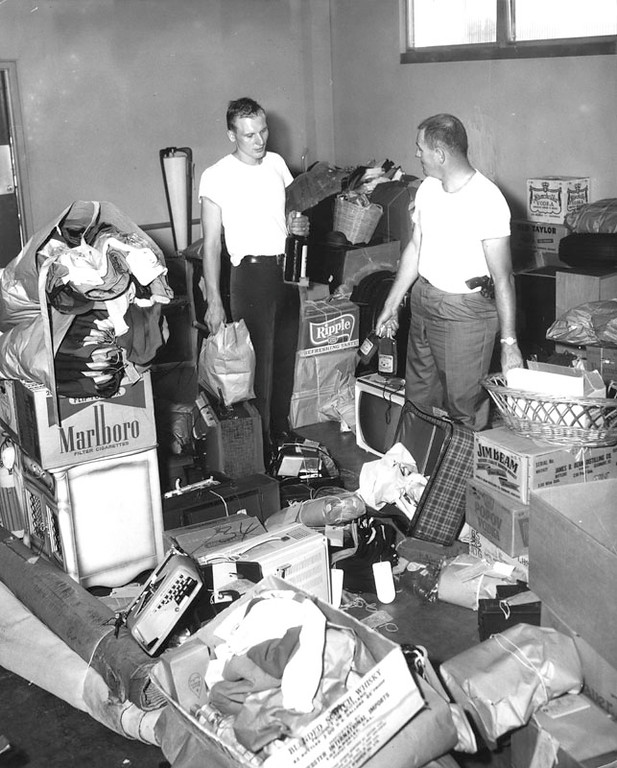. Detectives D.F. Ward (left), and R.R. Pignet inspect loot recovered from automobiles in the riot area, at University Police Station. Loot included clothes and many other items. Photo dated: August 17, 1965. (Los Angeles Public Library)