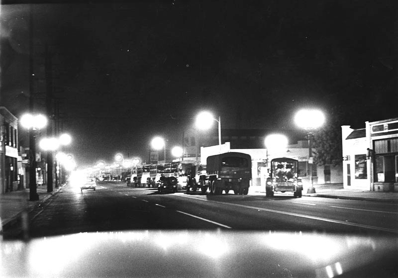 . A convoy of National Guard vehicles cruise down Broadway. Photo dated: August 14, 1965.  (Los Angeles Public Library)