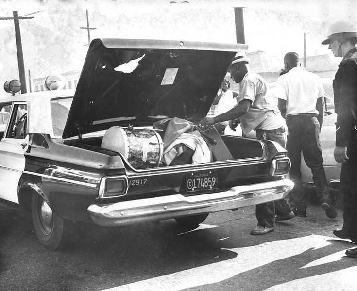 . Police recover loot taken from a pawn shop at 103rd and Grandee, in Watts. Photo dated: August 13, 1965. (Los Angeles Public Library)