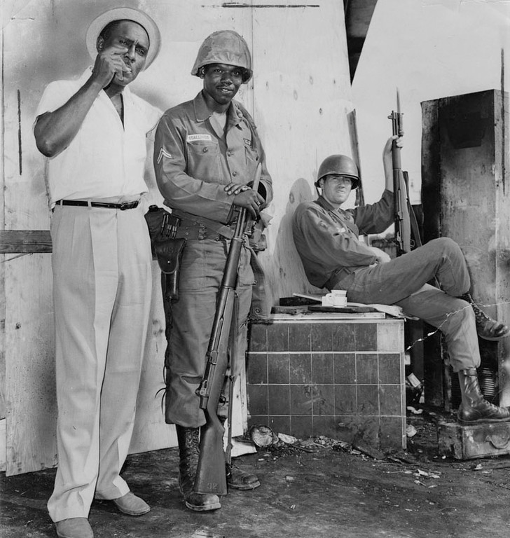 . Harvey Ramsey, 46, a city of Los Angeles employee, of 700 E. 103rd Place, which is in the riot area, talks with National Guard Cpl. Richard Stallings of San Francisco. \'Somebody got \'em all stirred up,\' says Ramsey.  Photograph dated August 18, 1965. (Los Angeles Public Library)
