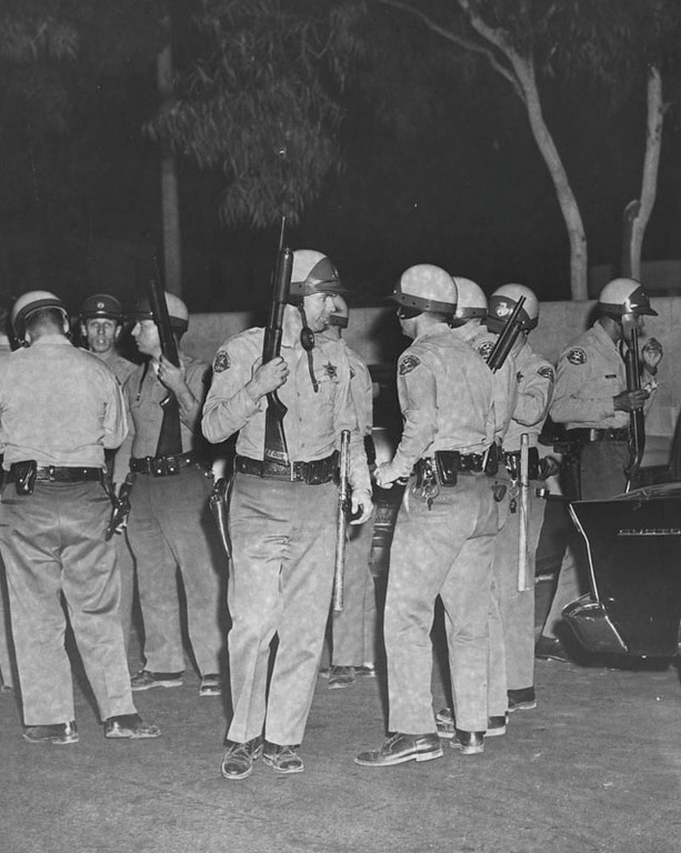. Deputies shown with 12-guage shotguns getting ready to hold the Firestone Sheriff Station under arms in anticipaton of attack by rioters in the Watts area. Photo dated: August 14, 1965 (Los Angeles Public Library)