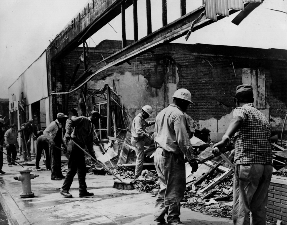 . circa 1965: Workmen sweeping up debris left by the Los Angeles Watts riots on 103rd Street.   (Photo by Keystone/Getty Images)