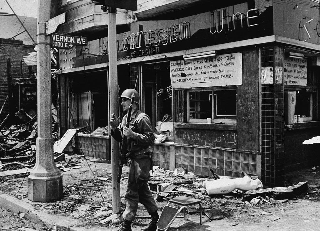 . An armed National Guard patrolman leans against a street sign, smoking a cigarette and standing in rubble following the Watts riots, Los Angeles, California, August 1965. (Photo by Hulton Archive/Getty Images)
