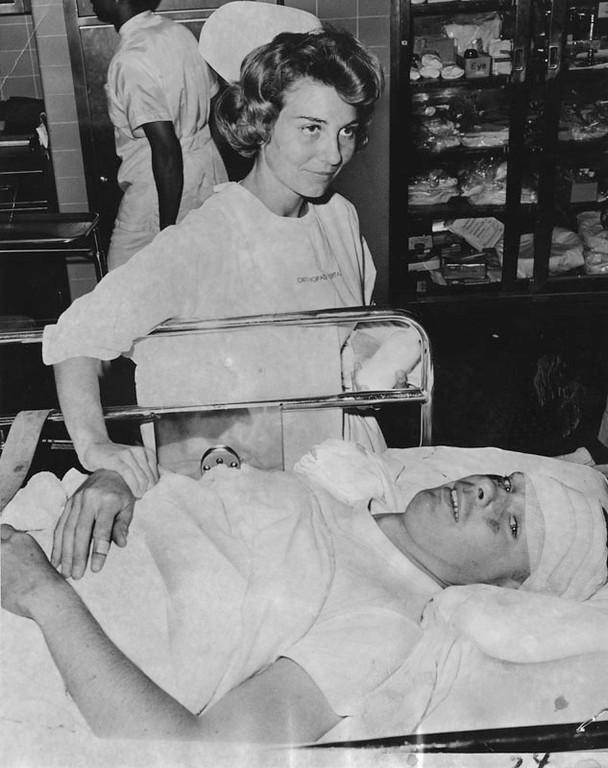 . A car rammed through a human chain of guardsmen during the rioting in Watts. Photo shows Wayne Stewart with nurse Karen Lumetta. Stewart got a broken leg when the auto hit. Photo dated: August 14, 1965.  (Los Angeles Public Library)