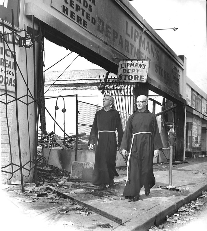 . Two priest walk by the exterior of which once was Lipman\'s Department Store. The store was looted and destroyed by fire during the rioting in Watts. Photo dated: August 18.1965.  (Los Angeles Public Library)
