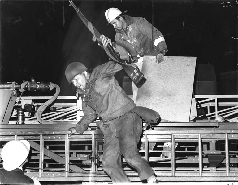 . Pfc. Barry Bertani of Walnut Creek and the 49th Natonal Guard Division leaps off fire truck at 47th and Broadway, as they arrive at a fire. Guardsmen furnished protection to firemen harassed by snipers in the rioting areas of Watts. Photo dated: August 16. 1965. (Los Angeles Public Library)