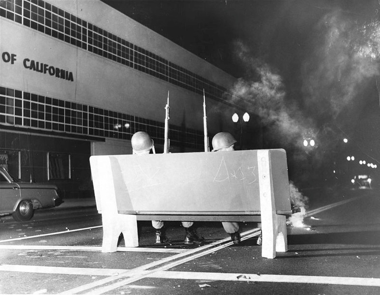 . 1965 Watts Riots: Two National Guardsmen sit on a bench in the middle of the road. The guardsmen are keeping watch over the buildings and area. (Los Angeles Public Library)