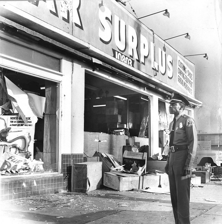 . A security guard looks over extensive damage to a War Surplus store on Avalon Boulevard and 108th Street. Store was smashed and looted just before dawn, by wild-eyed youths who roamed through the area in packs during the Watts Riots. Photo dated: August 13, 1965. (Los Angeles Public Library)