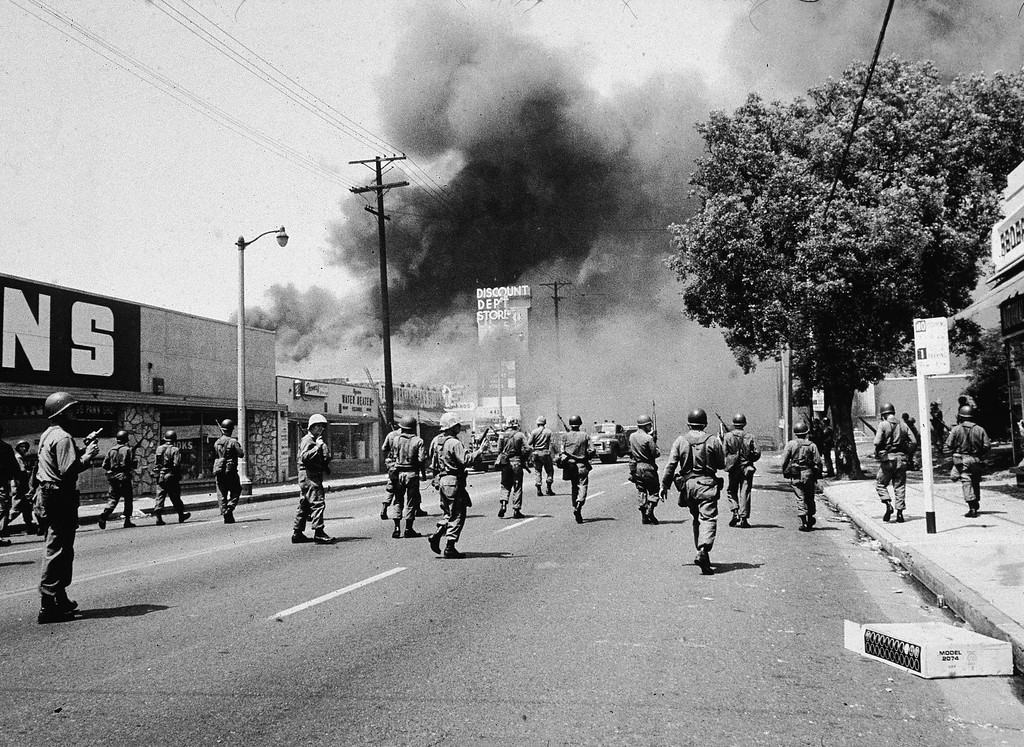 . Armed National Guardsmen march toward smoke on the horizon during the Watts riots in Los Angeles, California, August 1965. (Photo by Hulton Archive/Getty Images)