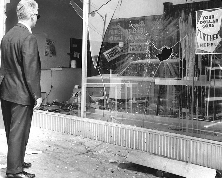 . A man stands in front of what used to be the General Store at 1807 103rd Street in downtown Watts. Windows were broken and store was looted during the rioting in the Watts area. Photo dated: August 17, 1965.  (Los Angeles Public Library)
