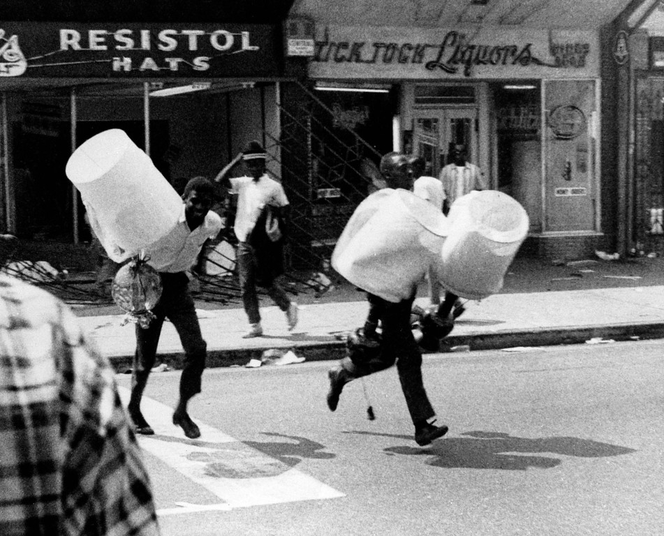 . Two youths carrying lamps from a looted store, run down a street, in the Watts section of Los Angeles August, 13, 1965. The six days of violence left 34 dead and resulted in $40 million of property damage. (AP Photo)
