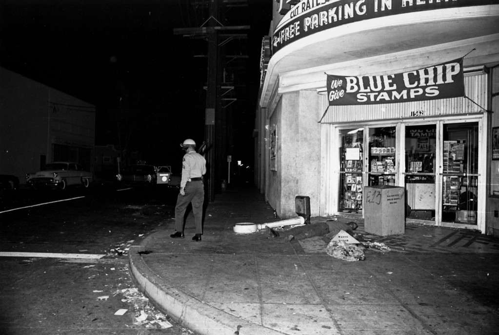 . An armed policeman walks away from the body of a man killed on the streets of Los Angeles during the Watts race riots, 11th-15th August 1965. (Photo by Harry Benson/Express/Getty Images)