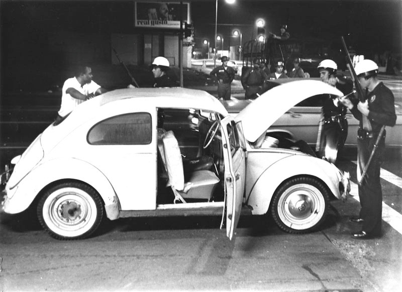 . Driver of a Volkswagen is detained, while two officers search the trunk for any stolen loot from rioting in the Watts area. National Guardsmen with rifles stand in the background. Photo dated: August 16, 1965.  (Los Angeles Public Library)