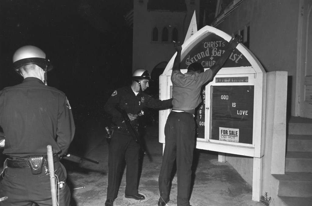 . A suspect being searched by two armed police during the Watts race riots in Los Angeles, California, 11th-15th August 1965.   (Photo by Harry Benson/Getty Images)