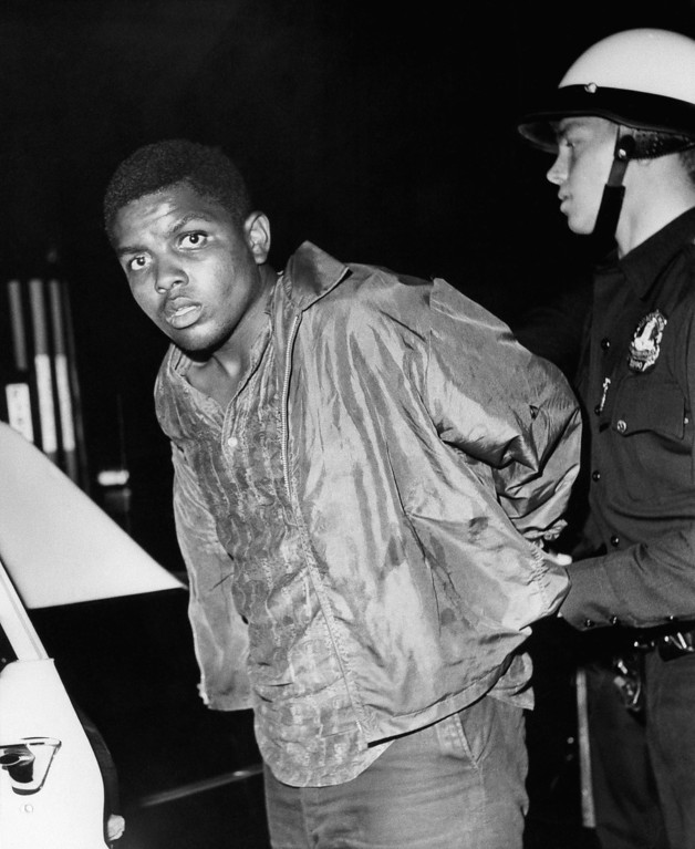 . An unidentified man is led to a police car in the Watts section of Los Angeles August 13, 1965, after his arrest during the second night of rioting. Several hundred police officers worked through the night in an attempt to control violence that included shooting, stone-throwing, looting and arson. (AP Photo)