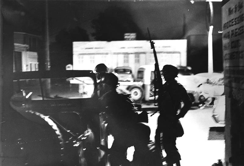 . Photo shows National Guardsmen on alert. A short time earlier they shot and killed a man who failed to halt for them. More than 8 bulletholes were counted in the windshield at 103rd and Compton, during the riots in the Watts area. Photo dated: August 14, 1965.  (Los Angeles Public Library)