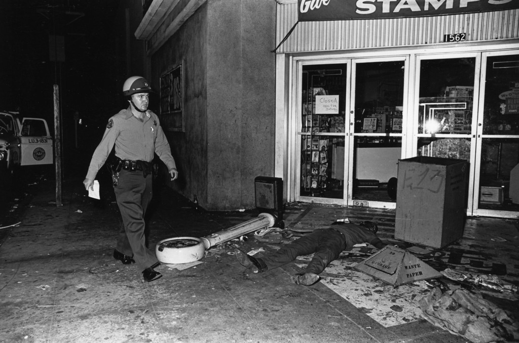 . An armed policeman and a victim of street violence, during the race riots in Los Angeles, California, 11th-15th August 1965.  (Photo by Harry Benson/Express/Getty Images)