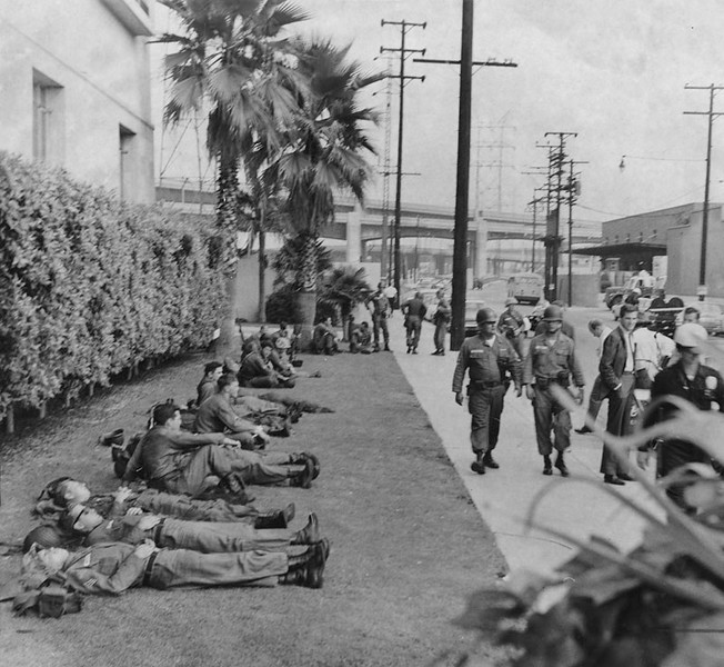 . National Guardsmen find a little time to relax during the Watts Riots. The men are on the lawn in front of the jail, in Lincoln Heights. Photo dated: August 16, 1965.  (Los Angeles Public Library)