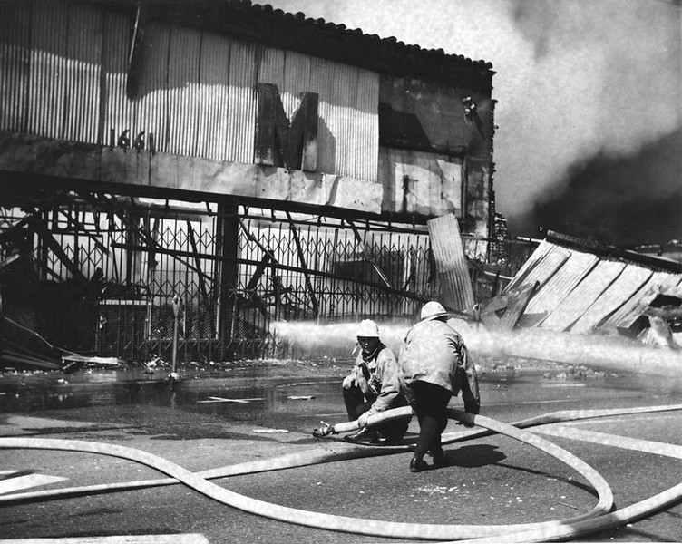 . Two firemen man a hose outside Martin\'s Furniture Store at 1661 East 103rd Street in Watts. Store was set afire during the rioting in Watts. Photo dated: August 13, 1965. (Los Angeles Public Library)
