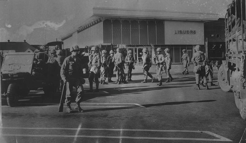 . A National Guard unit moves into the Safeway store at Vernon and Figueroa on August 14, 1965. It was the last supermarket in the general area left standing during the Watts Riot.  (Los Angeles Public Library)