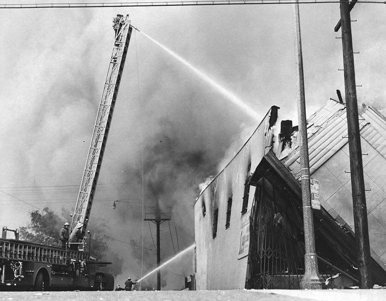 . 1965 Watts Riots: Store collapses as firemen try to control a 6 block blaze at 43rd and Central, in Watts.  (Los Angeles Public Library)
