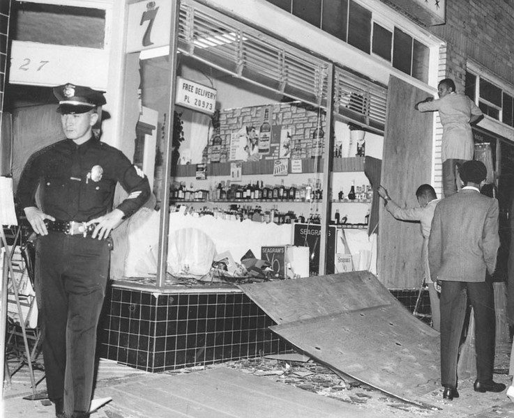 . 1965 Watts Riots: Police Sgt. Stanley Uno guards a liquor store at 8527 S. San Pedro Street after rioters smashed windows and looted the store. Glass litters the sidewalk as workers start boarding up the windows.  (Los Angeles Public Library)