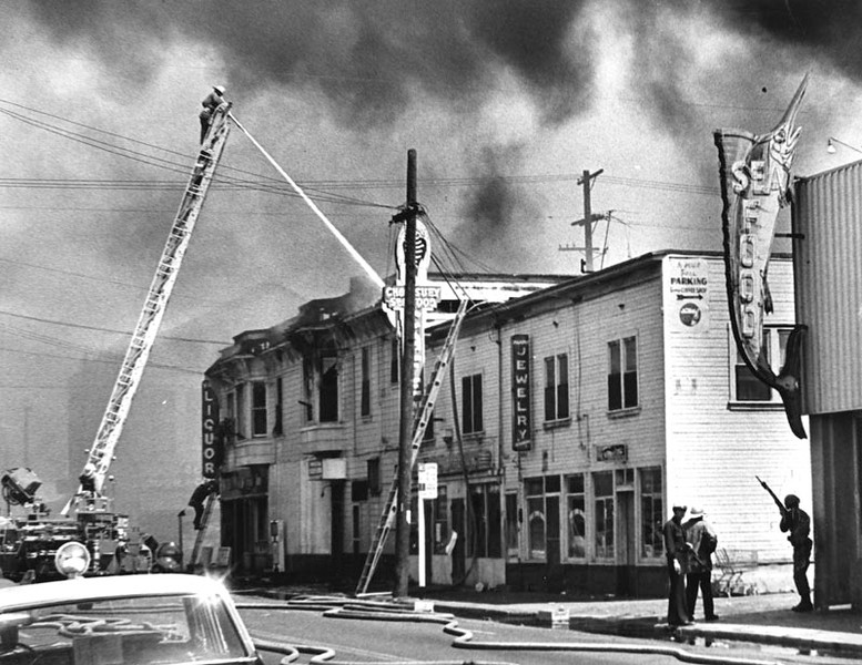 """. 1965 Watts Riots: A fireman on a tall ladder aims water at fire on the rooftop of a building complex in Watts. Corner building has a Liquor store, A Chop Suey and Seafood restaurant and a Jewelry Store. Two other firemen on a shorter ladder can be seen on the left, by the \""""Liquor\"""" sign. Officers with rifles stand guard by the alley.  (Los Angeles Public Library)"""