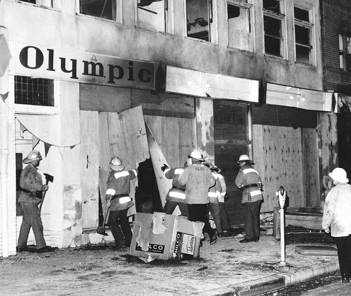. Firemen with axes tear at boards covering a building in Watts. Photo dated: August 16, 1965.  (Los Angeles Public Library)