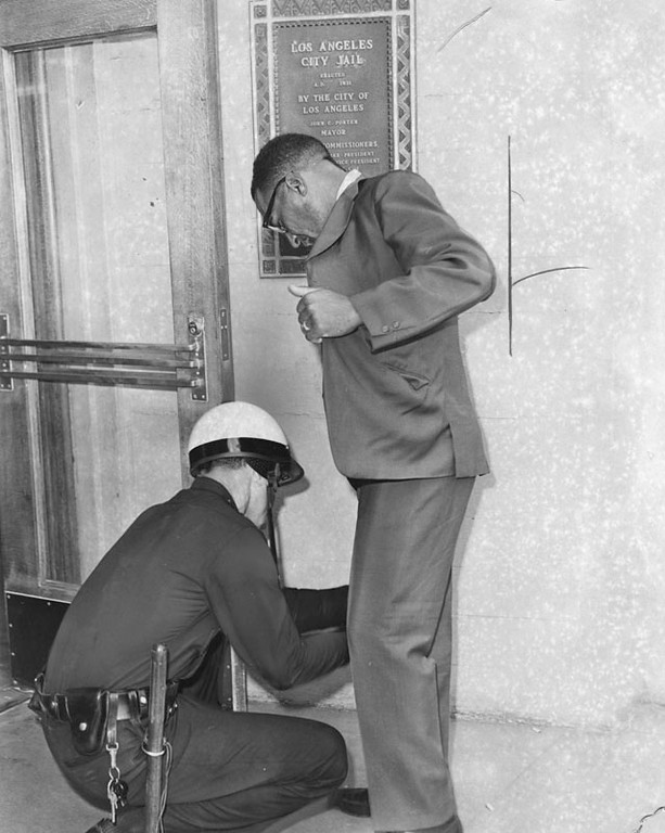 . C.J. Fitzpatrick is searched by officer C.J. Conrad at the entrance to Lincoln Heights Jail. Fitzpatrick went to the building in sarch of his son, Ralph, 18. The youth had been jailed on a burglary charge. Photo dated: August 17, 1965.  (Los Angeles Public Library)