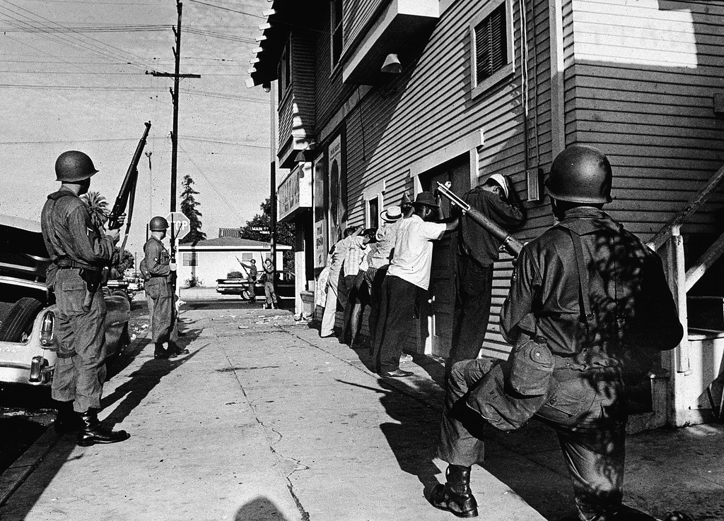 . Armed National Guardsmen force a line of Black men to stand against the wall of a building during the Watts race riots, Los Angeles, California, August 1965. (Photo by Hulton Archive/Getty Images)