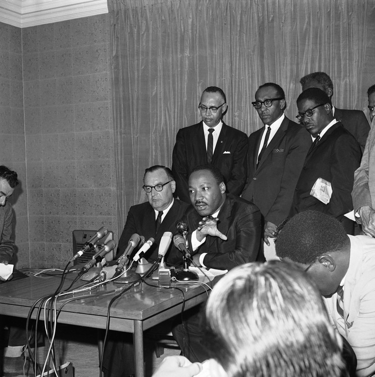 . Dr. Martin Luther King Jr., right, tells a news conference in Los Angeles, Aug. 19, 1965 that he has asked Gov. Edmund Brown Sr., left, to visit the Watts area of the city and talk to the people.  (AP Photo/Harold P. Matosian)