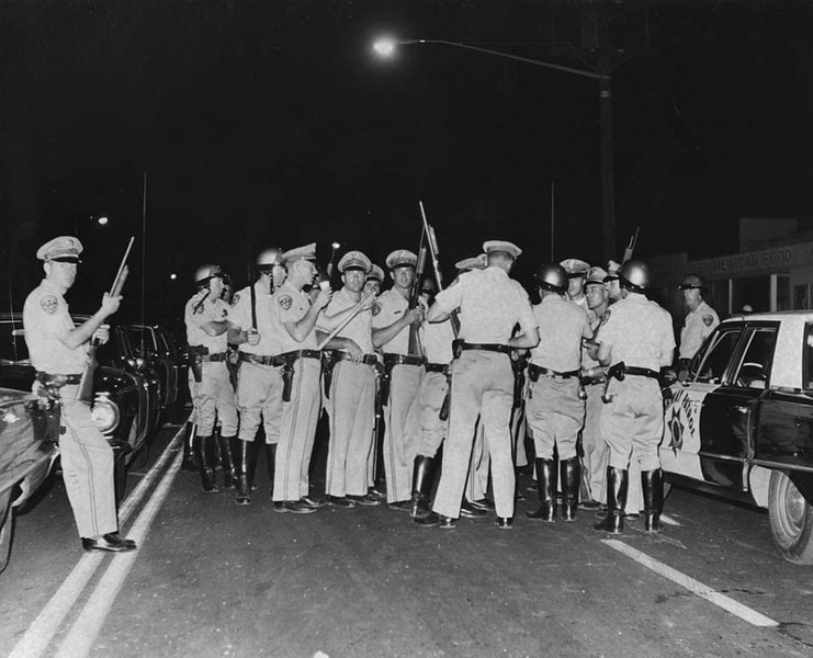 . CHP officers with shotguns get ready to man the lines at 112th Street and Avalon Boulevard, during the rioting in the Watts area. Photograph dated August 13, 1965.  (Los Angeles Public Library)
