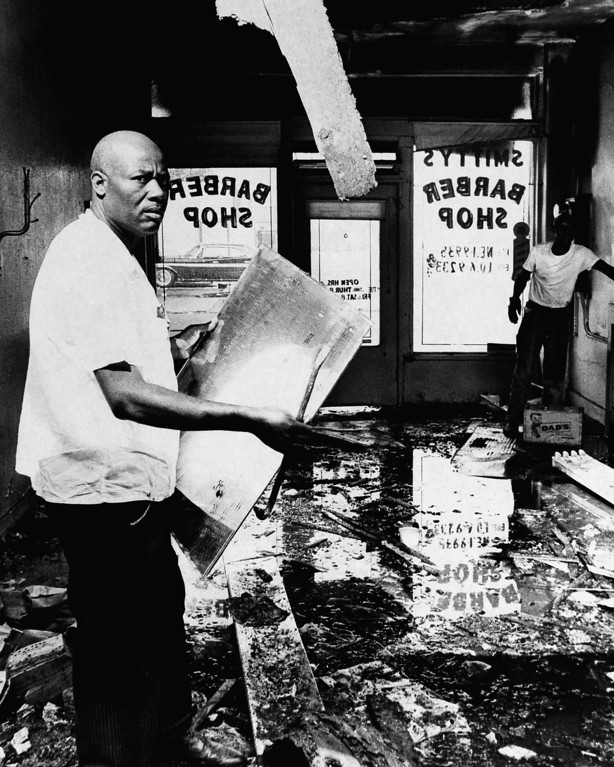 . A.Z. Smith, a victim of the Los Angeles riots, checks the damage to his barber shop in the Watts area of Los Angeles, Aug. 17, 1965. Business establishments owned by whites were the usual targets of looters and arsonists. Smith was one of the few blacks caught up in the turmoil. (AP Photo)