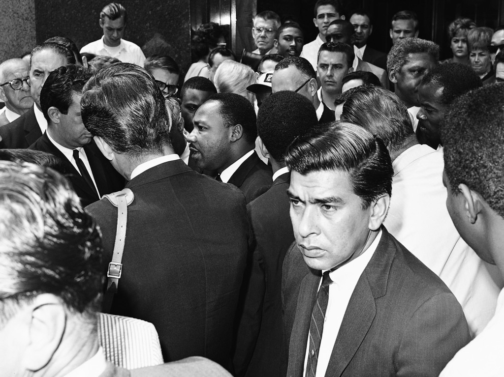 . Dr. Martin Luther King Jr. is surrounded by newsmen and passersby as he moves through downtown Los Angeles on August 18, 1965 on a series of conference about the city�s prolonged racial disturbances.   (AP Photo/Harold Filan)