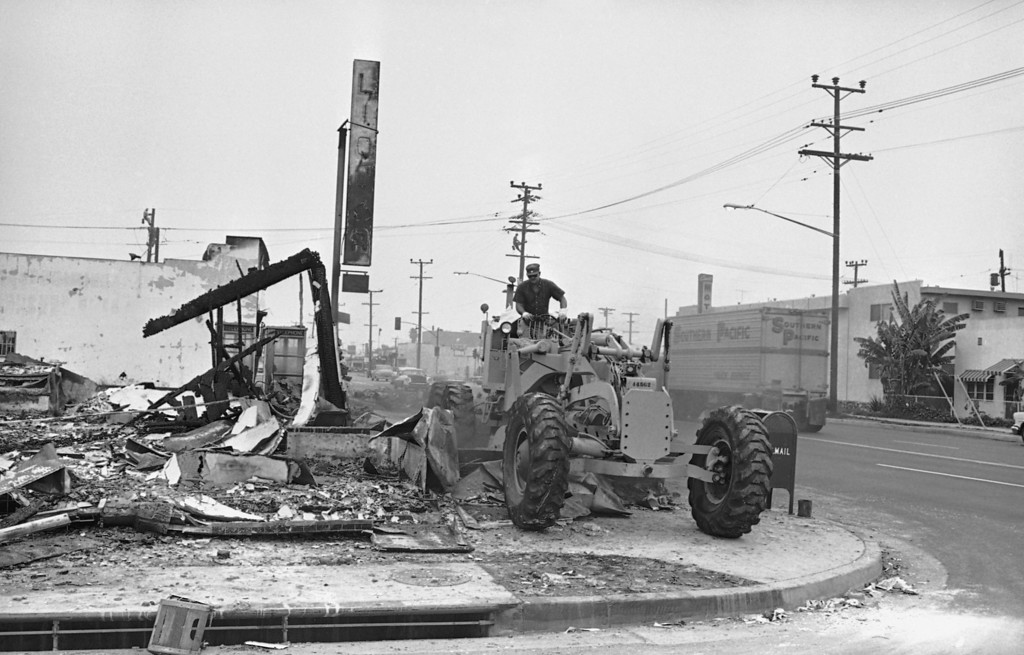 . The massive job of cleaning up gets underway as a bulldozer clears debris from a fire-gutted store off the sidewalk in Watts, Los Angeles, Aug. 18, 1965. (AP Photo/Ellis R. Bosworth)