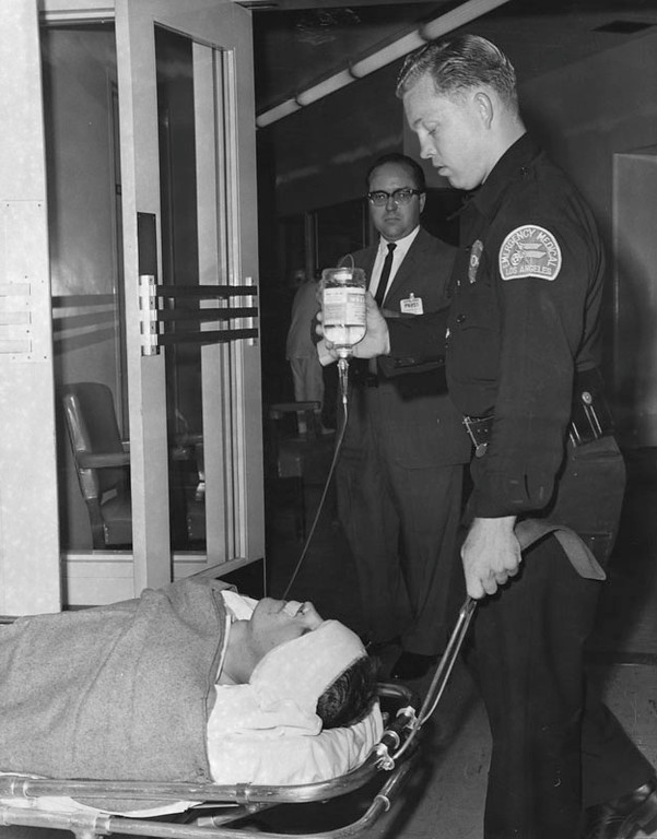 . Ambulance driver Walter Gray prepares hit-and-run victim, Pvt. James L. Kopenick for transfer to General Hospital following treatment at Central Receiving Hospital. Kopenick was one of two National Guardsmen hurt when a hit-run driver collided with their jeep at Hooper and Vernon Avenues in the Watts area. Photo dated: August 17, 1965.  (Los Angeles Public Library)
