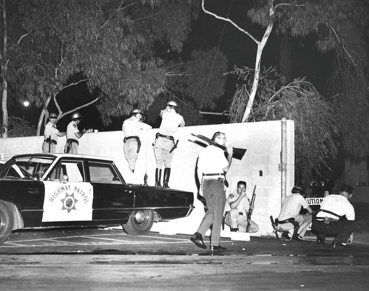 . Deputies are shown with 12-guage shotguns, holding the Firestone Sheriffs Station under arms in anticipaton of attack by rioters in the Watts area. Photo dated: September 13, 1965. (Los Angeles Public Library)