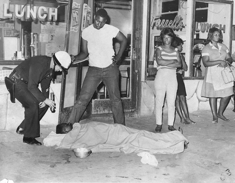 . Officer aids Bruce Williams, shot during the rioting. Williams was later removed by ambulance on August 15, 1965.  (Los Angeles Public Library)