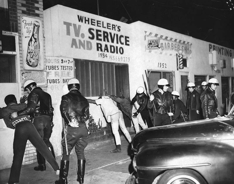 . 1965 Watts Riots: Police search for weapons in the 1900 block on East 103rd Street in Watts. Police patrolling the riot area stopped men who were driving around late at night and then released them when no weapons were found. (Los Angeles Public Library)
