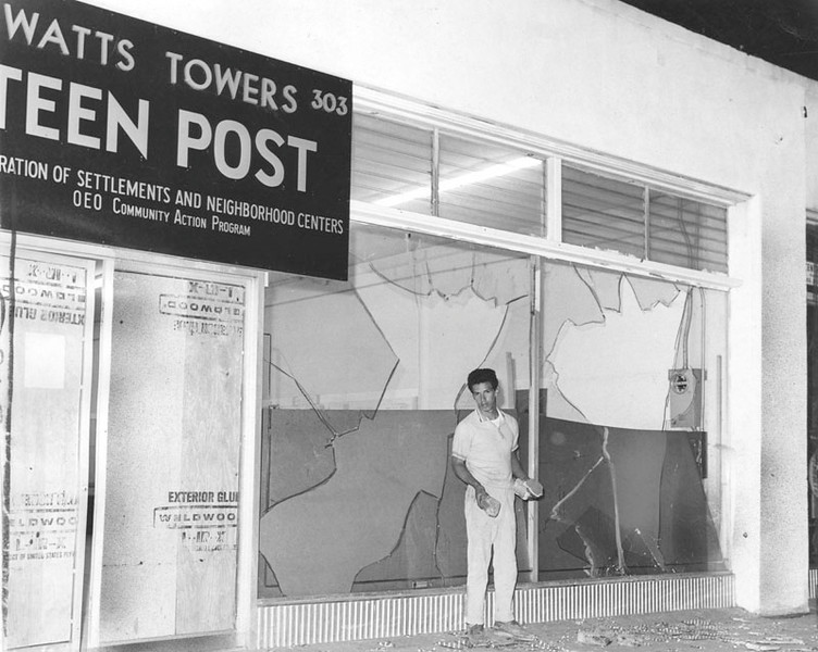 . 1965 Watts Riots: Vandals smashed two windows at the Watts Towers Teen Post at 1807 East 103rd Street, according to the police. John Estrada, 20, is shown surveying the scene. He helped clean out the debris at the site. (Los Angeles Public Library)