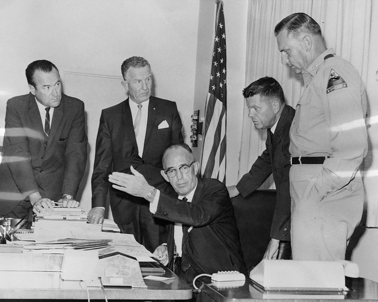 . Los Angeles Police Chief William H. Parker holds a conference in his office during the Watts riots. Present were: Deputy Chief Tom Reddin, Deputy Chief Roger Murdock, Supervisor Warren Dorn, and Major General Charles Ott. Parker is seated at the desk in this August 13, 1965 photo. The rioting began August 11 and lasted six nights.  (Los Angeles Public Library)