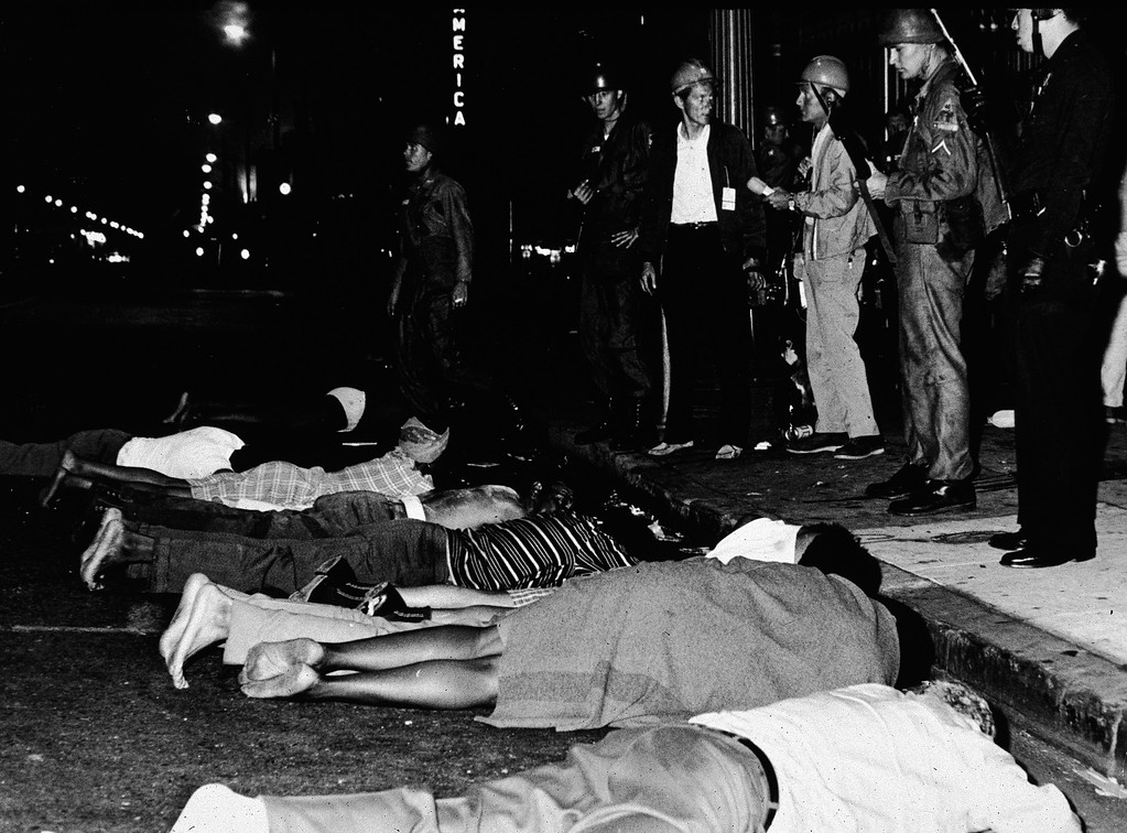 . Armed police stand by as rioters lay face down in the street during the Watts race riots, Los Angeles, California, August 1965. (Photo by Hulton Archive/Getty Images)